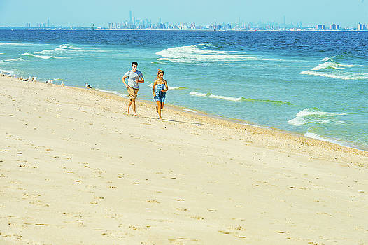 Alexander Image - Young couple running on Sandy Hook Beach, New Jersey, USA.